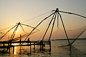 Chinese fishing nets hanging in the water at sunset, Fort Kochi, Cheena valas (Chinese fishing nets) at Fort Kochi (Fort Cochion), Kerala, India.
