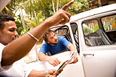 Taxi driver pointing out directions to backpacker in car, Varkala, Kerala, India