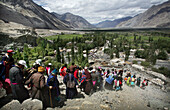Ladakhi people and Buddhist monks walking down the mountain in a line, Nubra Valley, Leh Ladakh, India