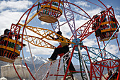 Man manually operating small ferris wheel at a fun fair in Leh, Human-powered big wheel (merry-go-round) at fun fair during the  800 year old birthday celebration of the Buddhist Drukpa Lineage, Naro Photang Shey (Shey Monastery), Leh, Ladakh, Himalayas,