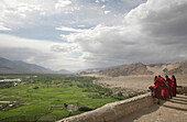 Buddhist monks on rooftop at Thikse Monastery looking over Indus Valley, Gompa, near Leh, Ladakh, India