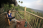 A  woman using a wireless laptop computer on the balcony of a remote bamboo hut, Near Mawlynnong, East Khasi Hills, Meghalaya, North East States, India