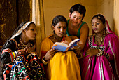 Westerner and women in saris and jewellery looking at guide book, Jaipur, Rajasthan, India