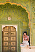Woman chatting on mobile phone in decorated entrance of the City Palace, Jaipur, Rajasthan, India