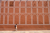 Woman with backpack walking past wall of the City Palace, Jaipur, Rajasthan, India