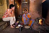 Western woman chatting with Indian lady as she cooks chapatis and prepares meal, Jaipur, Rajasthan, India