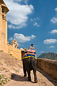 Tourist on elephant going up path at Amber Fort, Near Jaipur, Rajasthan, India