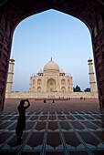 Silhouette of tourist in arch photographing the Taj Mahal at dusk, Agra, Uttar Pradesh, India