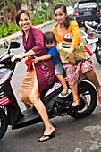 Two women and boy sitting on motorbike, Ubud, Bali, Indonesia