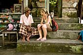 Female tourist sitting with local man, Ubud, Bali, Indonesia