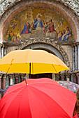 Tourists in the rain in Venice, Saint Mark's Basilica (Basilica San Marco), Venice, Italy.