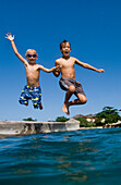 Two children jumping off platform into the sea, Discovery Bay, Jamaica