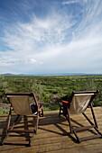 Two Deck chairs on wooden deck overlooking grassland, Masai Mara, Kenya