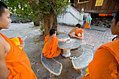 Novice monks relaxing playing checkers, Luang Prabang, Northern Laos