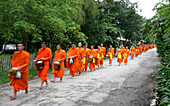 Monks walking in line collecting donations, Blurred Motion, Luang Prabang, Laos