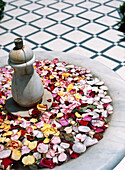 Flower blossoms in fountain on tiled floor, Marrakech, Morocco