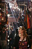 A woman browsing clothes and handbags in the souk, Shopping in the Medina, Marrakech, Morocco.