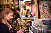 Young woman browsing for antiques in a market stall in the souk, Shopping in the Medina, Marrakesh, Morocco.