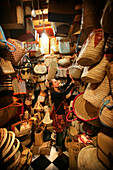 Young woman browsing wicker baskets and handbags in the souk, Shopping in the Medina, Marrakesh, Morocco.