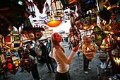 A woman browsing for Moroccan lanterns in a market stall in the souk, Shopping in the Medina, Marrakesh, Morocco.