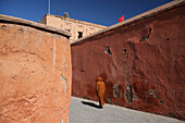Local man wearing long-hooded cloak known as a djellaba, worn by both male and females, blends into the colourful walls near the Royal Palace in Marrakesh/Marrakech, Morocco, Marrakesh/Marrakech, Morocco.