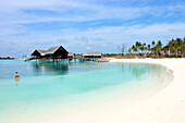 View of bungalos with swimmer, Maldives