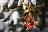 Jingle bells Christmas ornament hanging outside in snow