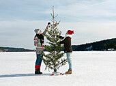 Couple preparing christmas tree