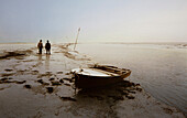Two men with a rowboat in a tidal creek, East Frisian Wadden Sea, East Friesland, North Sea, Lower Saxony, Germany, Europe