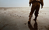 Man with rubber boots, mudflat hiking tour, East Frisian Wadden Sea, East Friesland, North Sea, Lower Saxony, Germany, Europe