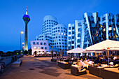 Restaurant terrace, Gehry buildings and Rheinturm tower in the evening, Neuer Zollhof (architect: F.O. Gehry), Media harbour, Duesseldorf, Rhine river, North Rhine-Westphalia, Germany, Europe