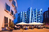 Restaurant terrace and  buildings in the evening, Neuer Zollhof, Media harbour, Duesseldorf, Rhine river, North Rhine-Westphalia, Germany, Europe