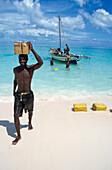 Man carrying box on head on beach, Vamizi Querimbas, Mozambique