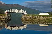 White footbridge over lake with reflections, Loen. Stryn. Nordfjord. Norway