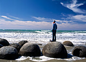 Woman standing on one of the Moeraki Boulders, South Island, New Zealand