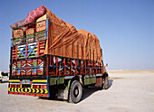 Truck on desert highway, Oman