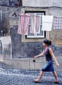 Woman walking by washing line, Alfama, Alfama, Lisbon, Portugal