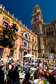 People at cafe tables in square in front of cathedral and Palacio Episcopal, Malaga, Andalucia, Spain