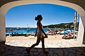 Girl walking under arch near beach in Calella fishing village, Costa Brava, Catalunya, Spain