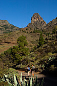 Hikers passing the Roque de Agando, Integral Nature Reserve, Island of La Gomera, Island of La Gomera. Canary Islands. Spain