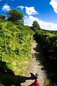 Leg of male walker walking along country footpath, North Devon, Exmoor, England