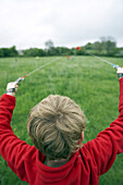 Young boy launching red kite in a grassy field, England