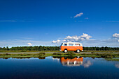 Orange campervan driving past pond, New Forest, Hampshire