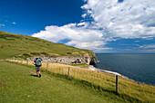 Man walking along coastal path, Near Worth Matravers, Purbeck, Dorset, UK