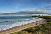 Embleton Bay with Dunstanburgh Castle in distance, Northumberland, England, UK