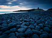 Embleton Bay and Dunstanburgh Castle in distance, night, Northumberland, England, UK