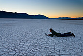 Man lying down using laptop on the salt pans at dawn, Death Valley, California