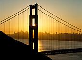 Yellow sunrise behind the Golden Gate Bridge with skyline behind, San Francisco, California