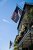 Ornate wrought iron balcony with flower hanging baskets and two US flags flying, French Quarter, New Orleans, Louisiana