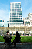 Skyscrapers surrounding Bryant Park and people enjoying the sun, Garment District, Manhattan, New York, USA